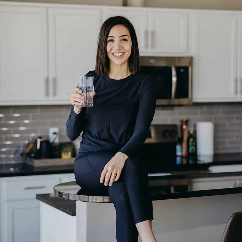 Weight loss dietitian sitting on kitchen counter drinking water